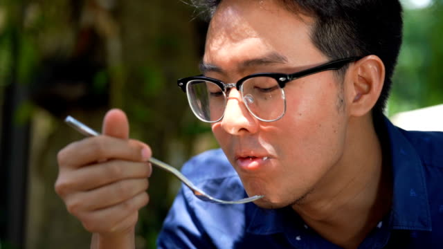 slo mo - tilt up shot of man eating avocado with rice cracker - quinoa salad stock videos & royalty-free footage