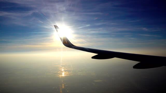 4K Tilt up shot van Morning Sky voor zonsondergang met Flying Airplane Wing