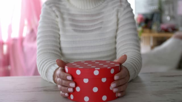 tilt up shot of smiling young woman holding a polka dot gift box - dog knotted in woman stock videos & royalty-free footage