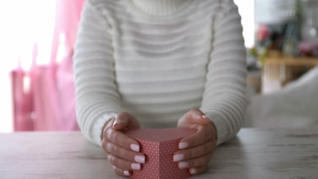 tilt up shot of smiling young woman holding a polka dot heart shaped gift box - polka dot stock videos & royalty-free footage