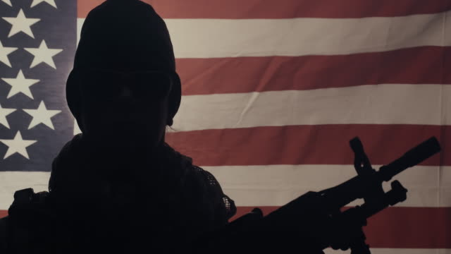 tilt up shot of soldier holding machine gun with usa flag in background. - military recruit stock videos & royalty-free footage