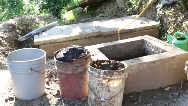a tilt up shot of three buckets with dung in them at a biogas production in a rural area near pilate haiti - afro caribbean ethnicity stock videos and b-roll footage