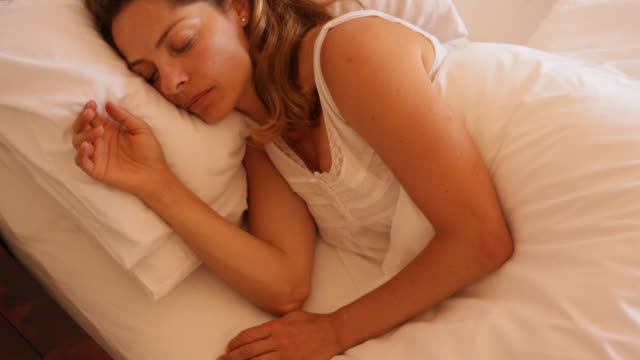 Tilt up shot of woman asleep in bed