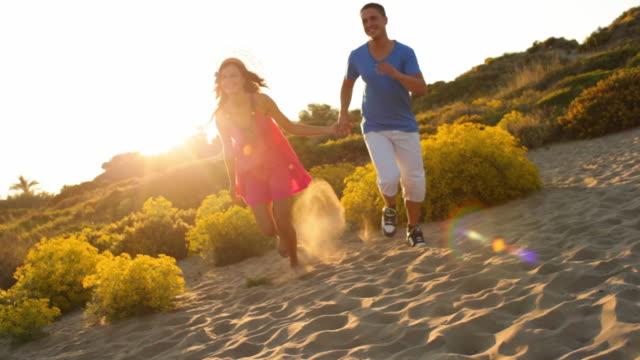 vídeos y material grabado en eventos de stock de tilt up shot of young couple running on sand dunes in sunset - encuadre de tres cuartos