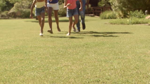 tilt up shot on family in park running towards camera - 4人点の映像素材/bロール