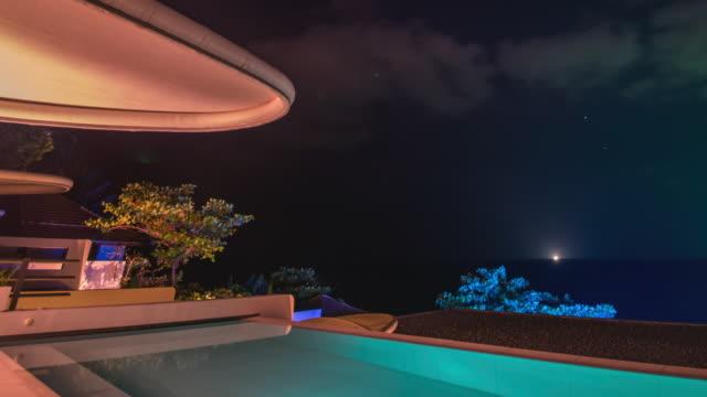 tilt up shot time-lapse night scenery of illuminating pool villa in thailand - bangkok stock-videos und b-roll-filmmaterial