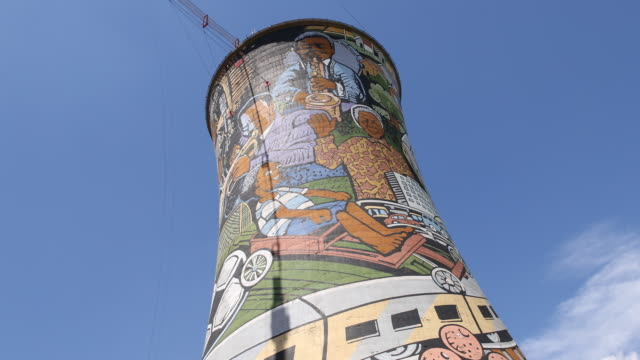 A tilt up showing the colorfully painted cooling towers of the Orlando power station with a bungee jumping bridge in Soweto a township of...