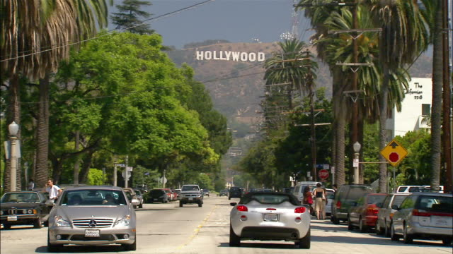 Tilt up silver car driving along street with Hollywood sign in background / Los Angeles, California