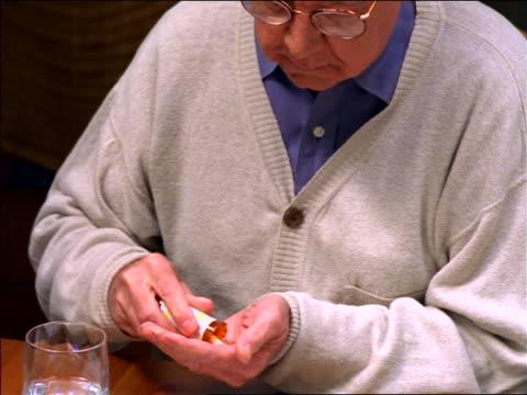 tilt up sitting senior man reading medication bottle + taking pills + drinking water - taking medicine stock videos & royalty-free footage