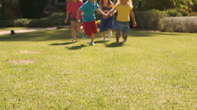vídeos de stock e filmes b-roll de tilt up slow motion shot of five children running towards camera in park. - 4 5 anos