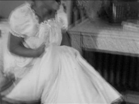b/w 1957 tilt up smiling girl in pajamas raising pillow in front of bed / educational - pillow fight stock videos & royalty-free footage