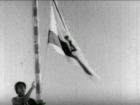 stockvideo's en b-roll-footage met b/w 1956 tilt up soldier raising israeli flag on pole / middle east / suez crisis / newsreel - 1956