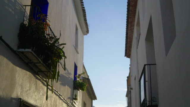 tilt up, stone house walls and balconies in narrow street with hills