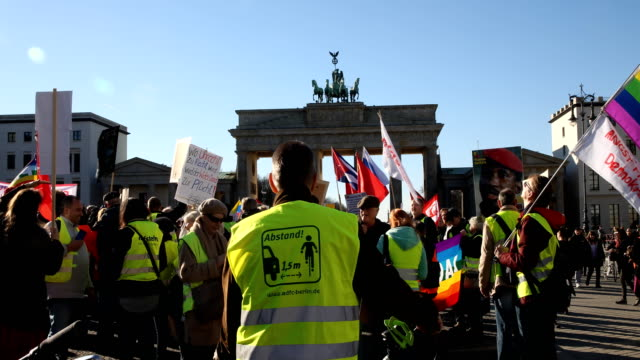 tilt up supporters of the new leftwing stand up movement gather at a demonstration which started at potsdamer platz and ended here at the brandenburg... - social movement stock videos and b-roll footage