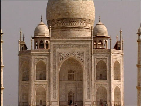 vídeos de stock e filmes b-roll de tilt up taj mahal as bird flies past dome roof structure agra - taj mahal
