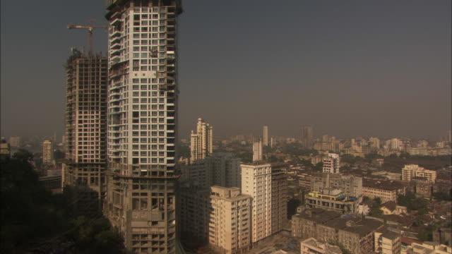 tilt up tall skyscraper under construction. available in hd. - erezione video stock e b–roll