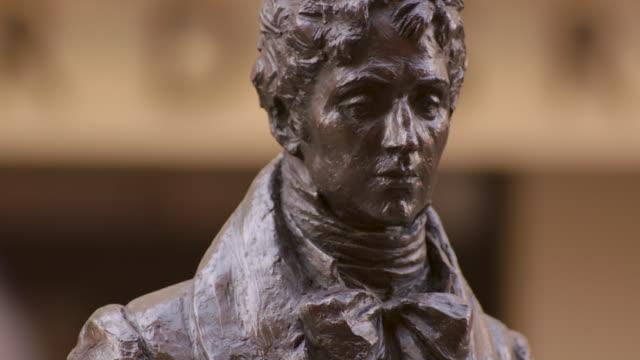 vídeos y material grabado en eventos de stock de tilt up, then down, a statue of beau brummell, 19th century fashion icon, on london's jermyn street, uk. - bronceado