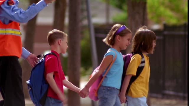 ms pan tilt up three children holding hands + crossing street with senior crossing guard holding stop sign - octagon stock videos & royalty-free footage