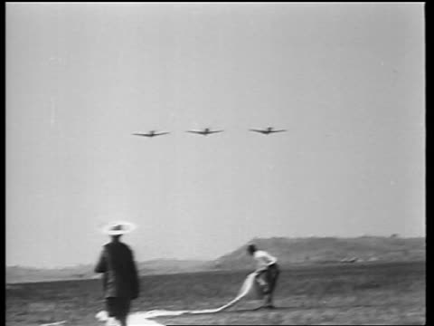 vídeos de stock, filmes e b-roll de b/w 1942 tilt up pan three fighter planes fly over people in straw hats in field / flying tigers / news - grupo pequeno de objetos