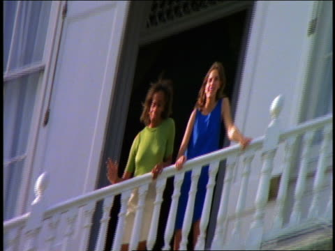 DISTORTED tilt up + tilt down 3 Black people walking up steps of mansion / 2 women on balcony above talking