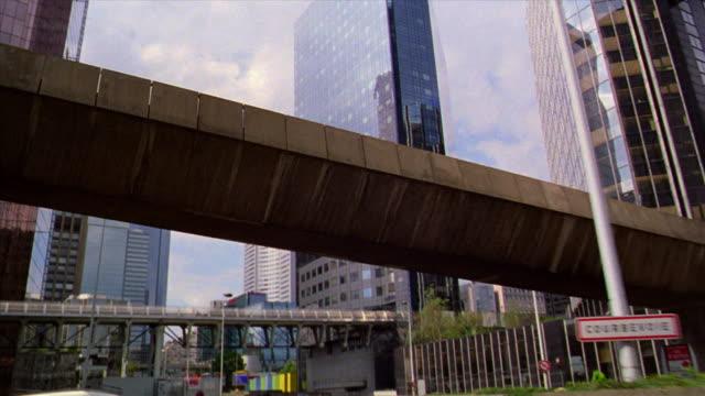 tilt up tilt down car point of view in traffic on highway past skyscrapers + office buildings in La Defense area / Paris