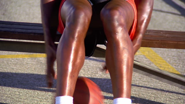 vidéos et rushes de ms tilt up tilt down from feet to face of bald shirtless black man sitting on bench dribbling basketball by feet - banc