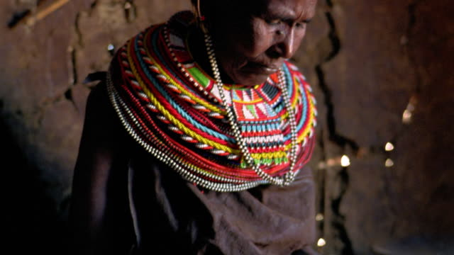 MS tilt up tilt down from hands of senior Masai tribeswoman beading to her face looking down / Kenya