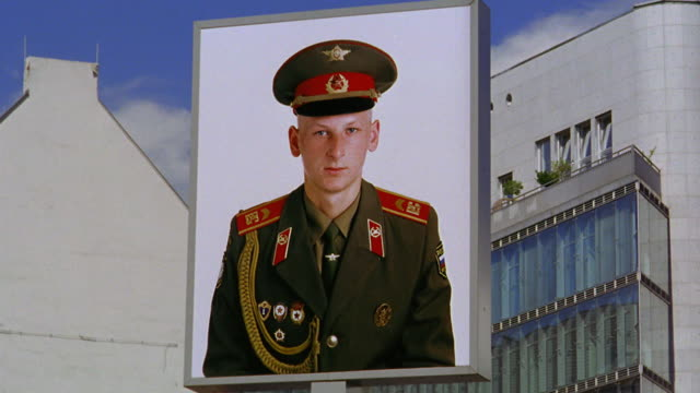 tilt up tilt down PAN from t-shirt to large poster of portrait of Russian soldier in uniform /Checkpoint Charlie