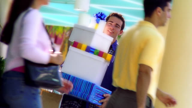 canted ms tilt up tilt down hispanic man walking with stack of gift boxes + dropping them / florida - war in afghanistan: 2001 present stock-videos und b-roll-filmmaterial
