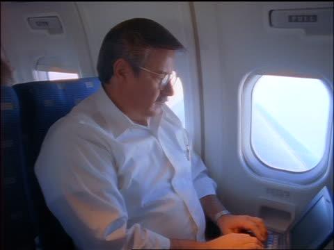tilt up + tilt down PROFILE man in eyeglasses sitting in airplane typing on laptop