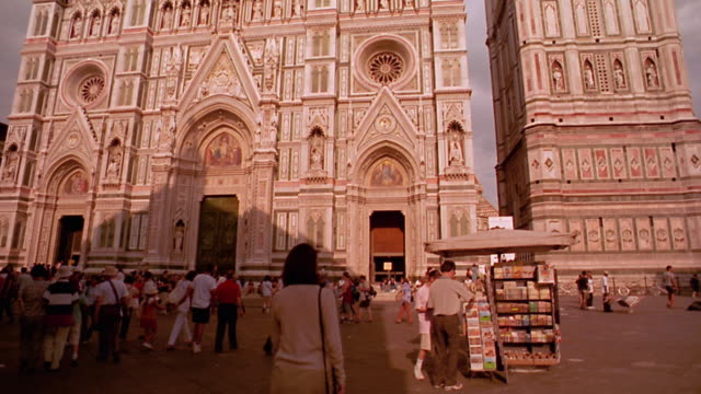 tilt up tilt down Santa Maria del Fiore (Duomo) with woman walking to street vendor in foreground / Florence, Italy