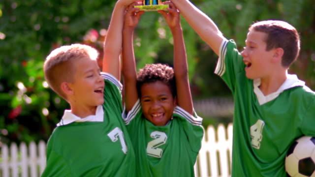 ms tilt up tilt down three boys in soccer uniforms lifting trophy in air outdoors / florida - jugendmannschaft stock-videos und b-roll-filmmaterial