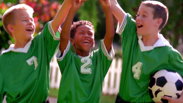 MS tilt up tilt down three boys in soccer uniforms lifting trophy in air + cheering / Florida