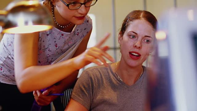 vidéos et rushes de ms pan tilt up tilt down two women talking + looking at computer in office / one woman nods - seulement des jeunes femmes