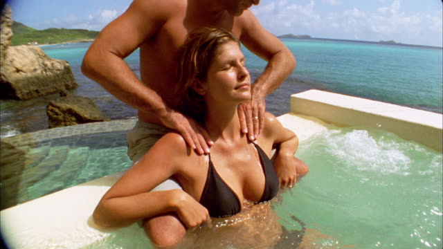 Tilt up tilt down woman receiving massage from man in hot tub overlooking ocean