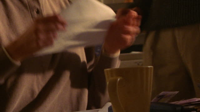tilt up tilt down woman sitting at kitchen table putting bills into envelopes + man answering phone - envelope stock videos & royalty-free footage