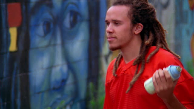 vidéos et rushes de ms tilt up tilt down zoom out zoom in young man with dreadlocks looking at wall, dancing, + holding spraypaint can / low angle - secouer