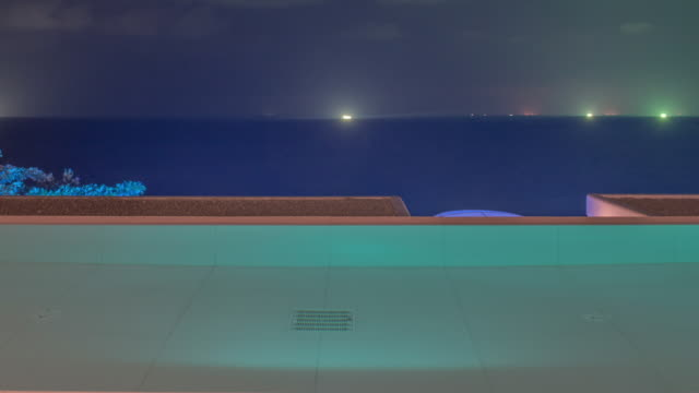 tilt up time-lapse night scenery of the sea over illuminating pool villa in thailand - infinity pool stock videos & royalty-free footage