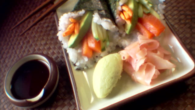 tilt up to a close-up of cone sushi with wasabi and ginger. - wasabi stock videos and b-roll footage