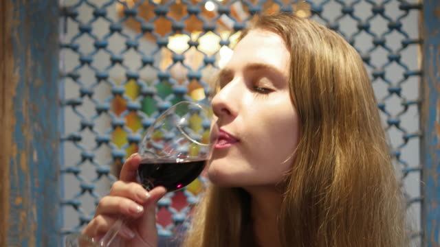 Tilt up to a super hot and attractive woman sipping a glass of wine
