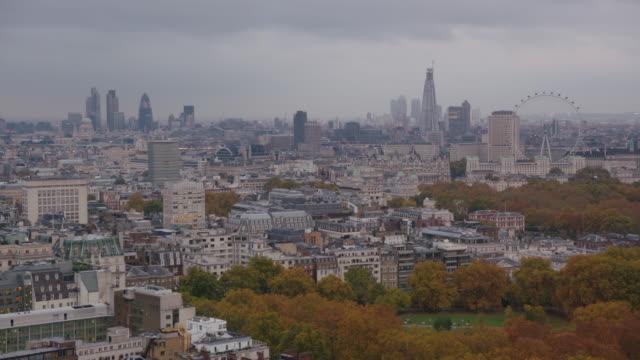 Tilt up to a wide, elevated shot of London's vast skyline as dusk settles, UK.