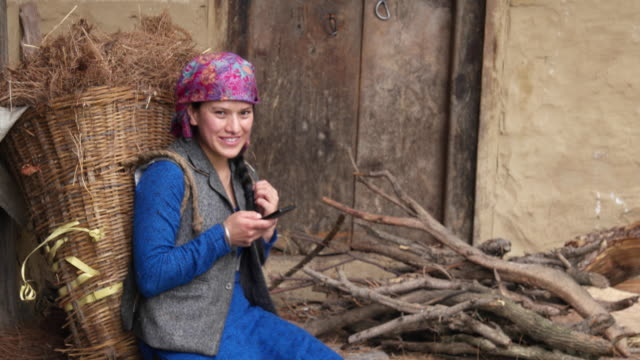 tilt up to a woman seated with a basket of hay on her back and using her mobile phone - shoulder ride woman stock videos & royalty-free footage