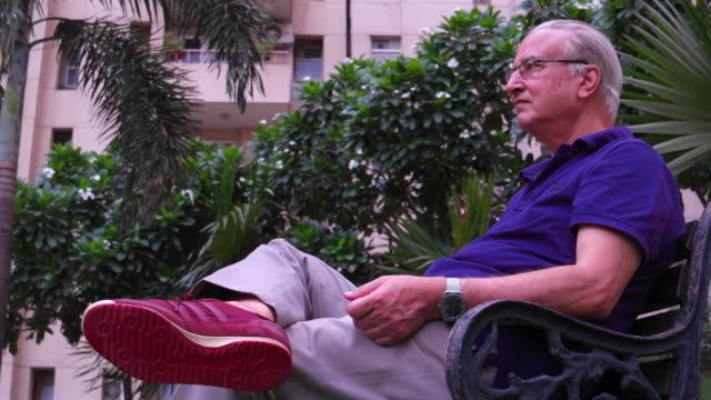 vídeos y material grabado en eventos de stock de tilt up to an elderly gentleman sitting in a public park on a bench - camisa de polo