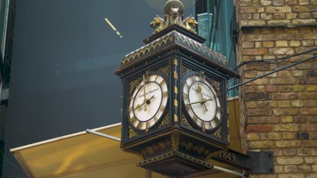 Tilt up to an ornate clock featuring brass horse heads at Camden's Stables Market