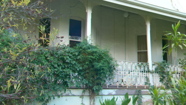 tilt up to bay window, white brick house, verandah with wrought iron railing on which a vine is growing. crack in brickwork over window - bay window stock videos & royalty-free footage