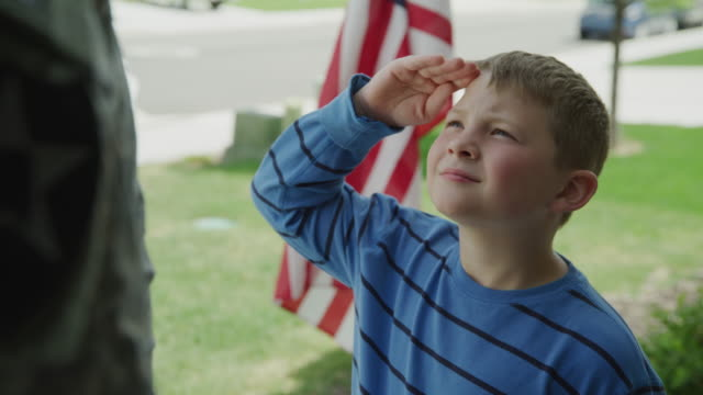 tilt up to boy saluting soldier father near american flag / lehi, utah, united states - saluting stock videos & royalty-free footage