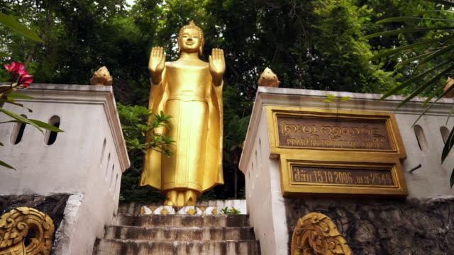 tilt up to buddha statue on mount phousi, luang prabang, laos - mudra stock videos & royalty-free footage