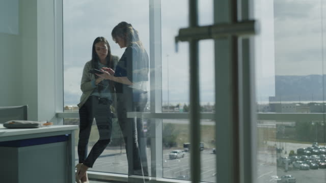 tilt up to businesswomen leaning on office window using digital tablet / pleasant grove, utah, united states - e mail stock-videos und b-roll-filmmaterial