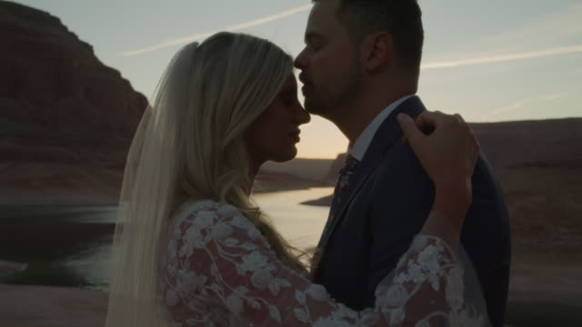 vídeos de stock, filmes e b-roll de tilt up to close up of bride and groom hugging near lake at sunset / lake powell, utah, united states - focus on foreground