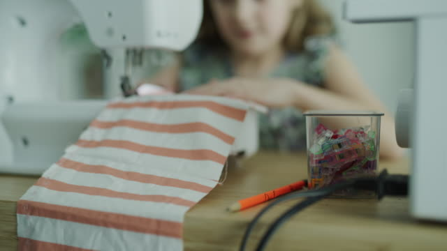 tilt up to close up of girl sewing fabric with sewing machine / lehi, utah, united states - lehi stock videos & royalty-free footage